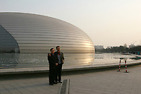 CHINA. Beijing. Two tourists posing for a photo. Outside view of the Grand National Theatre. Designed by French architect Paul Andreu, The Grand National Theatre is located near Beijing's central Tian'anmen Square. It is an enormous glass and titanium tear-drop-like bubble structure surrounded by water. As China's top art performance center, it covers a total floor space of around 180,000 square meters, including 130,000 square meters for the main building and 50,000 square meters underground facilities. 2008.