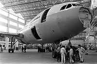 Usine de l'Aérospatiale de Saint-Martin-du-Touch, grand hall de montage. 5 février 1972. Vue en contre-plongée de l'Airbus A300 B (plan rapproché sur l'avant de l'avion) ; techniciens au pied de l'avion. Cliché pris lors du 1er déplacement tracté de l'avion encore en cours de montage.