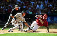 Apr. 11, 2010; Phoenix, AZ, USA; MLB umpire Mike Reilly looks on as Arizona Diamondbacks baserunner Justin Upton slides safely into third base ahead of the tag from Pittsburgh Pirates third baseman Delwyn Young in the fourth inning at Chase Field. Mandatory Credit: Mark J. Rebilas-