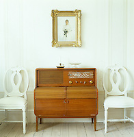 Lena Eriksson's wedding portrait, in an antique English frame, hangs above a 1950's vintage radio console