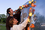 Couple hanging up lights on their silver 1965 Airstream Globe Trotter