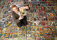 BNPS.co.uk (01202 558833)<br /> Pic: ZacharyCulpin/BNPS<br /> <br /> Auctioneer, Andy Wooller with the collection, he's pictured with the rarest and most expensive comic of <br /> collection a Fantastic Four number one that is valued at £2,500<br /> A huge comic collection immaculately accumulated over 60 years by a late fanatic has been found by his family. <br /> <br /> The vast archive of over 8,000 comics was amassed by bachelor Peter James who kept them in pristine condition at his home.<br /> <br /> He was introduced to comics by his mother as a young boy as she thought it would encourage him to read.<br /> <br /> He started collecting at the age of 10 and kept the magazines neatly stacked in boxes.