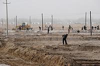 CHINA, autonomous province Xinjiang, uyghur worker prepare irrigation canals for a cotton plantation which belongs to a Han-chinese investor / CHINA, autonome Provinz Xinjiang, ausserhalb Kashgars, uigurische Arbeiter ziehen Bewaesserungsgraeben fuer eine Baumwollplantage am Rand der Taklamakan Wueste, die einem Han-chinesischen Investor gehoert