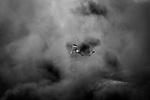 SHEJAIYA, GAZA: One of the Shebab is throwing rocks at Israeli soldiers while being hidden by the black smoke of the burning tires, on May 14, 2018. Israeli soldiers killed at least 52 Palestinians and wounded over a thousand as the demonstrations coincided with the controversial opening of the U.S. Embassy in Jerusalem.<br /> <br /> <br /> SHEJAIYA, GAZA: Un des Shebabs jette des pierres vers les soldats israeliens tout en étant camouflé par la fumée noire des pneus en feu, le 14 mai 2018. Les soldats israéliens ont tué au moins 52 Palestiniens et en ont blessé plus d'un millier lors de manifestations qui coïncident avec l'ouverture controversée de l'ambassade des États-Unis à Jérusalem.