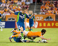 Seattle Sounders midfielder  Osvaldo Alonso (6) attempts to gain possession of the ball as Houston Dynamo midfielder Brad Davis (11) and Seattle Sounders midfielder Brad Evans (3) go down.  Houston Dynamo tied Seattle Sounders 1-1 on August 23, 2009 at Robertson Stadium in Houston, TX.