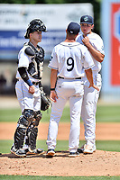 Asheville Tourists catcher Brian Serven (25), pitching coach Ryan Kibler (9) and starting pitcher Riley Pint (32) have a meeting on the mound during a game against the Rome Braves at McCormick Field on July 30, 2017 in Asheville, North Carolina. The Braves defeated the Tourists 7-3. (Tony Farlow/Four Seam Images)