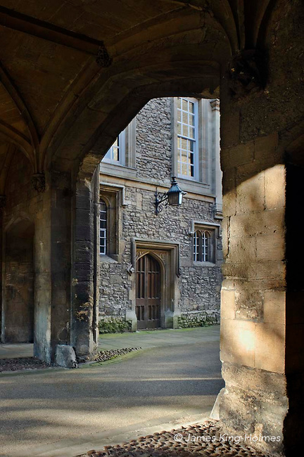 Door to the 16th Century Magistrate's Court seen through an arch in the Abbey Gateway in Abingdon-on-Thames, Oxfordshire, England. The courtroom, which still has windows dating from 1500, was also used as a theatre during the Elizabethan reign. It is now used as a music centre. This section of road is part of a Sustrans cycle route.