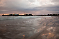 Stearns Wharf in Santa Barbara a low tide sunset with a storm brewing