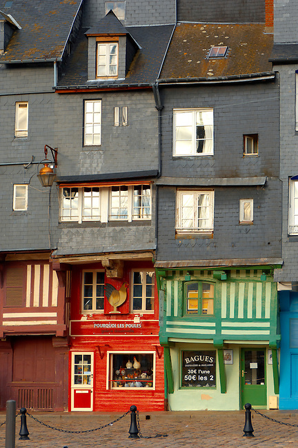 Harbour sided shops with an older couple looking in the window with arms around each other. Honfleur, Normandy, France.