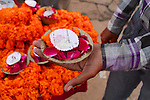 A man holds a puja offering of marigolds and rose petals he has just purchased. The small candle will be lit, and the offering gently placed in the holy Ganges River.