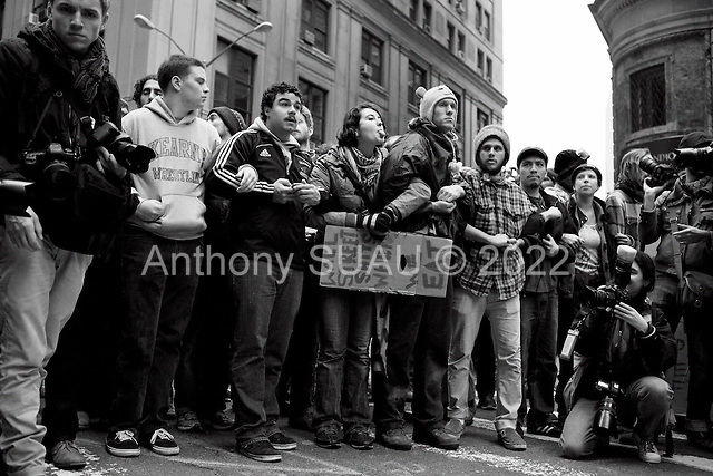 """New York, New York.November 17, 2011<br /> <br /> """"Occupy Wall Street"""" protesters mark the movement's two-month milestone by marching from Zuccotti Park, in mass, to various access streets surrounding the New York Stock Exchange, which the police had barricaded off. Yet instead of the police keeping protesters out, protesters locked down those entrances to Wall Street and the New York Stock Exchange creating havoc as the police made more then 240 arrests to try and keep the streets open to normal traffic.<br /> <br /> Demonstrators block the intersection at Williams Street and Exchange Place to disrupt business as usual on Wall Street while chanting against financial inequality. Police warn them to move or they will be arrested."""