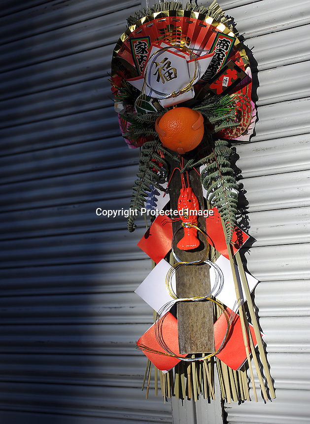 A Shogatsu Kazari,  New Year ornament hangs on the door of a residential home in Tokyo, Japan.  The Japanese celebrate the first three days of the New Year which are public holidays and days of rest of visits to shrines and temples.