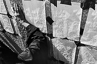 """Iraq. Baghdad. The """" Committee for free prisoners"""" establishes various lists of the people which were executed by Saddam Hussein regime. Families come everyday to read the lists and collect informations on their loved parents, hoping to know their whereabouts. A woman dressed in a black veil reads the dead people list taped on the wall. © 2003 Didier Ruef"""