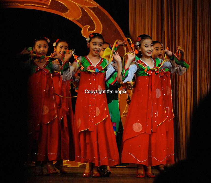 """Children of the privileged perform at the Children's Palace and School, Pyong Yan North Korea. North Korea is one of the last great dictatorships where, """"Our Dear Leader"""" Kim-Jong-il and his father Kim Il-sung """"The Great Leader"""" are worshipped and there is complete control of people who are constantly reminded of the evil deeds of the the west and USA."""