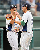 Hitting coach Joel Chimelis (11), left,  of the Lexington Legends high-fives shortstop Jiovanni Mier (3) after a win against the Greenville Drive on June 5, 2011, at Fluor Field at the West End in Greenville, S.C. Photo by Tom Priddy / Four Seam Images