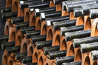 A big stack of bottles stored laying down stacked piled high in terracotta earthenware tube containers. Detail of bottle necks. Vita@I Vitaai Vitai Gangas Winery, Citluk, near Mostar. Federation Bosne i Hercegovine. Bosnia Herzegovina, Europe.