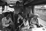 """Paul and Linda McCartney Wings Tour 1975. Paul and Linda on the tour bus with their daughter Mary McCartney on Paul's knee. Paul is talking to a member of the backing group brass section. Linda is talking to manager Alan Crowther. England. The photographs from this set were taken in 1975. I was on tour with them for a children's """"Fact Book"""". This book was called, The Facts about a Pop Group Featuring Wings. Introduced by Paul McCartney, published by G.Whizzard. They had recently recorded albums, Wildlife, Red Rose Speedway, Band on the Run and Venus and Mars. I believe it was the English leg of Wings Over the World tour. But as I recall they were promoting,  Band on the Run and Venus and Mars in particular."""