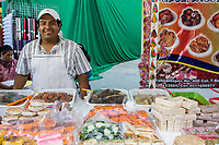 Oaxaca, Mexico, North America.  Day of the Dead Celebrations.  Candy Salesman, Vendor.  Visits to the Cemetery take on a carnival, family atmosphere as parents treat their children to sweets, candies, toys, and amusement rides.  San Miguel Cemetery, Oaxaca.