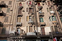 People watch protesters from balconies of their apartments in central Cairo. Continued anti-government protests take place in Cairo calling for President Mubarak to stand down. After dissolving the government, Mubarak still refuses to step down from power.
