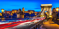 Iconic Szechenyi Chain bridge, stone lions, and royal palace lit up during twilight, with beautiful light trails from car traffic, Budapest Hungary