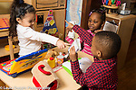 Education Preschool 3-4 year olds pretend play area playing store two girls and a boy, pointing and holding papers they are using for money