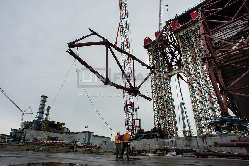 Workers of Chernobyl Nuclear Power Plant carefully placing part of arch's support on it's place. On the background - 4th reactor and concrete wall to provide workers protection from radiation.