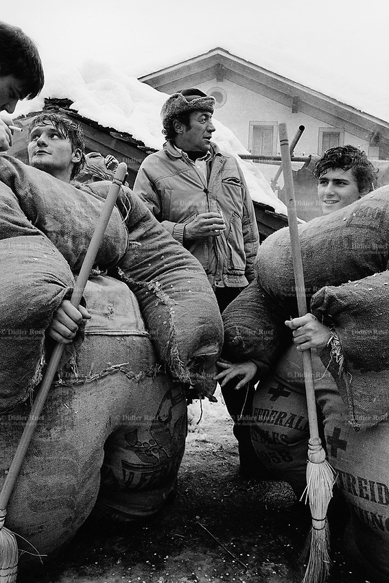 "Switzerland. Canton Valais. Evolène. Hèrens valley. Carnival. Young men, called ""Empaillés"", wear jute clothes filled with hay in traditional costumes. The clothes of the stuffed (Empaillés) are made with recycled bags of flour. Several hours are necessary to fill with hay the bags which constitute their disguise. © 1995 Didier Ruef"
