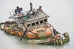 Rogue River, Gold Beach, Oregon; a rusty, delapidated tug boat, resting on the river bottom, where the Rogue River empties into the Pacific Ocean, after years of neglect and weather damage