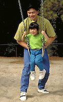 ASIAN-AMERICAN FATHER AND DAUGHTER PLAYING ON SWINGSET IN THE PARK. FATHER AND DAUGHTER. OAKLAND CALIFORNIA.