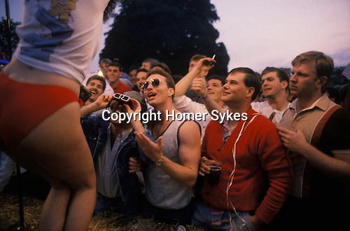 Mildenhall, Suffolk. 1980's<br /> On a make shift stage outside the Bird in Hand, American servicemen from the USAF base RAF Mildenhall, enjoy a beer filled evening watching local girls take part in a wet T-shirt competition.