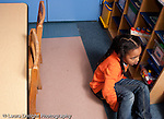 Educaton preschool 4-5 year olds girl sitting on floor while the other children dance to music (not visible) sad islolated horizontal