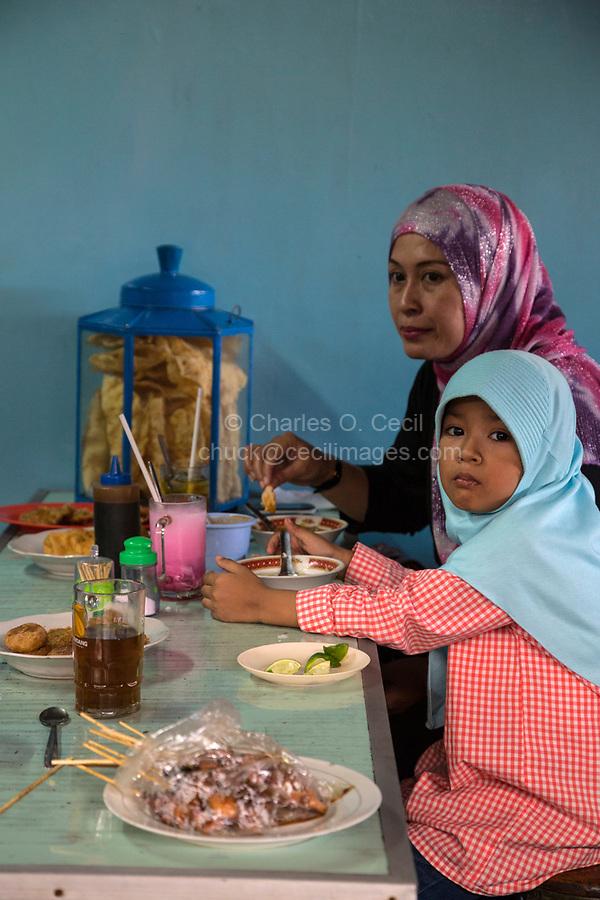 Yogyakarta, Java, Indonesia.  Mother and Daughter Having Lunch, Beringharjo Market.