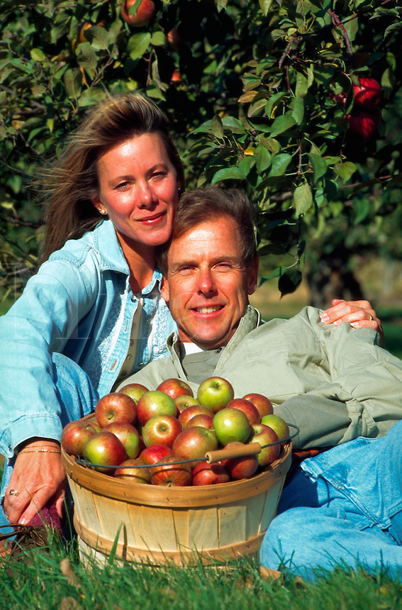 Couple posing with a basket of apples by apple tree.