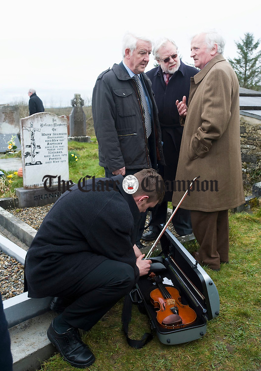 The next generation.... Liam O Connor, son of Mick O Connor, seen chatting with Tony Mc Mahon and Seamus Mc Mathuna, puts away his fiddle after playing at the graveside of Joe Ryan in Inagh following the burial. Photograph by John Kelly.