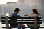 young woman arguing with young man on park bench