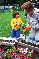 Planting flowers with grandma, little boy showing worm to older woman senior citizen, intergenerational gardening and learning in the backyard