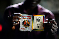 A man holds up MDC (Movement for Democratic Change) and Zanu-PF membership cards. Zanu-PF memebership was at one time required to receive food aid..