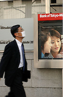 Salary men and office workers pass the Bank of Tokyo-Mitsubishi in the Tokyo banking and business district called Otemachi..