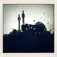 The dome and minarets of a mosque are silhouetted against a rainy sky in Kabul.