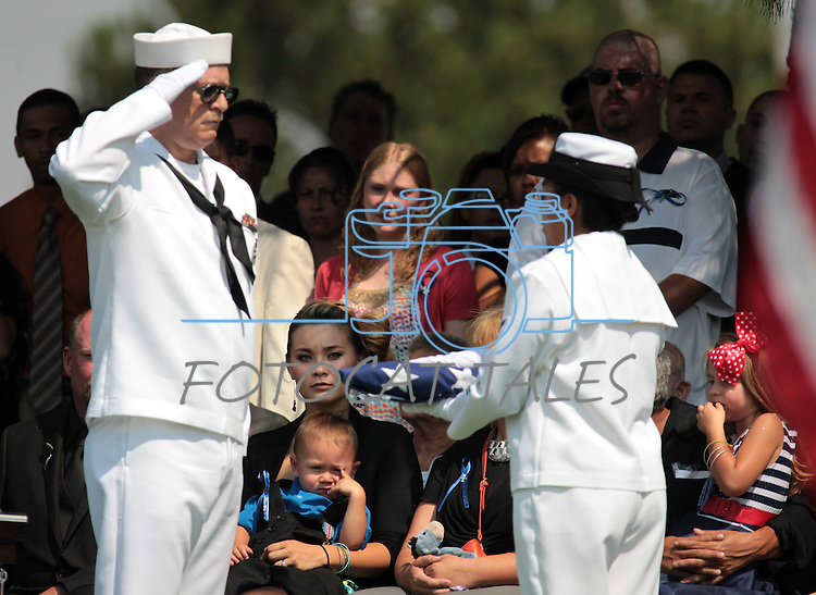 The family of Colorado shooting victim Jonathan Blunk, wife Chantel Blunk, center, holding her son Maximus, 2, and her daughter Hailey, 4, right, receive an American flag during a graveside service Friday, Aug. 4, 2012, in Reno, Nev. (AP Photo/Cathleen Allison)