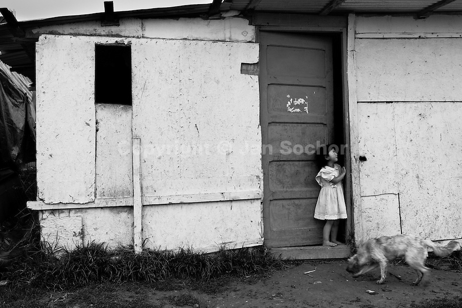 A displaced little girl lives with her mother in a dwelling made of chipboard in the shanty town of Ciudad Bolívar, Bogota, Colombia, 28 May 2010. With nearly fifty years of armed conflict, Colombia has the highest number of civil war refugees in the world. During the last ten years of the civil war more than 3 million people have been forced to abandon their lands and to leave their homes due to the violence. Internally displaced people (IDPs) come from remote rural areas, where most of the clashes between leftist guerrillas FARC-ELN, right-wing paramilitary groups and government forces takes place. Displaced persons flee in a hurry, carrying just personal belongings, and thus they inevitably end up in large slums of the big cities, with no hope for the future.