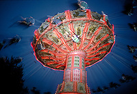 Amusement park ride enthusiasts fly through the air on chairs supended from a rotating carousel. Pittsburgh Pennsylvania United States Kennywood Park.
