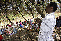 Kenya. Rift Valley province. Thugunui ( 45 km from Nakuru). A black Kikuyu man prays with a group of men and women standing under the shade of a tree. They are all IDPs. Internally displaced persons (IDPs) are people forced to flee because of the inter-ethnic strifes their homes but who, unlike refugees, remain within their country's borders. The Kikuyu are Kenya's most populous ethnic group. © 2008 Didier Ruef