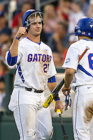 Florida Gators first baseman Peter Alonso (20) is greet by teammate Ryan Larson (66) after scoring against the Miami Hurricanes in the NCAA College World Series on June 13, 2015 at TD Ameritrade Park in Omaha, Nebraska. Florida defeated Miami 15-3. (Andrew Woolley/Four Seam Images)
