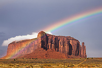 Storm light and rainbows over red rock buttes near entrance to Monument Valley, Utah.