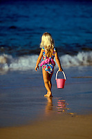 Young girl carries a bucket on the beach at Makena, Maui.