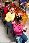 "Education Preschool Headstart group of children in pretend play area riding in ""bus"""