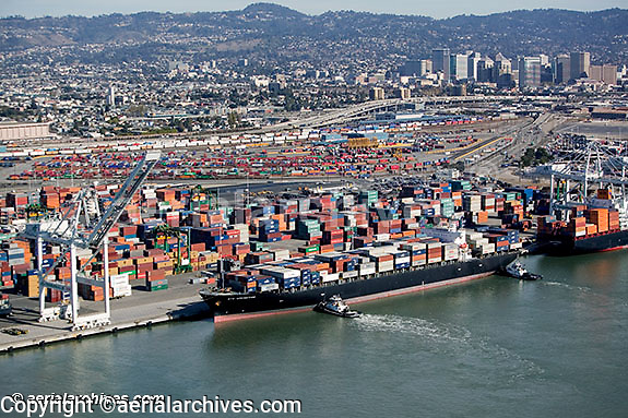 aerial photograph tugs holding containership in place Port of Oakland, California downtown Oakland in background