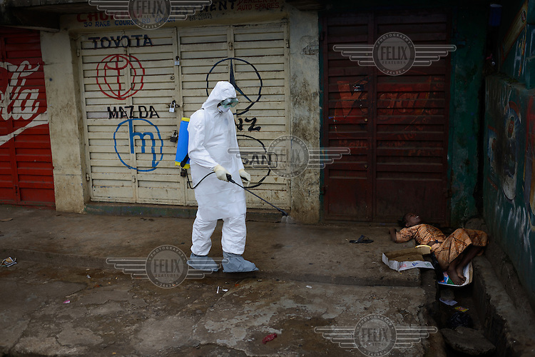An emergency health worker sprays chlorine next to a woman suspected of being infected with Ebola who is lying in an open sewer along the main street in Freetown. Emergency health services took hours to assist the woman and bring her to the hospital. The Sierra Leone government has declared a three day lockdown from 19 September in an attempt to prevent the further spread of Ebola across the country. <br /><br />Sierra Leone is one of three countries severely affected by the Ebola outbreak in West Africa which started in Guinea in December 2013 and spread to neighbouring countries including Liberia, Senegal and Nigeria. By late September 2014 it had killed close to 3,000 people across the region, 554 in Sierra Leone alone, making it the worst outbreak of the disease since it was identified in 1976. It is believed that the reported number of cases and deaths may well exceed the official figures due to an unwillingness to report cases among the population and a lack of resources to properly investigate suspected cases. Ebola virus disease (EVD) is a disease which affected humans and other primates and is transmitted by coming in contact with blood or other bodily fluids from infected persons or animals. It is believed that the disease is carried by fruit bats which can spread the virus without being affected themselves. In parts of West Africa, the consumption of so-called 'bushmeat' is thought to have caused the most recent outbreak.