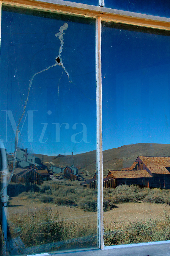 Reflections in the windows of one of the homes in the historic ghost town of Bodie.  Bodie was once bustling gold mining town, Bodie State Historic Park, California.